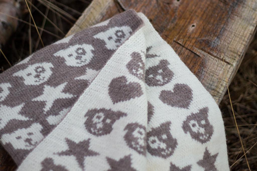 Starrfly er strikket i naturhvitt og lys beigemelert og har fylte motiv.